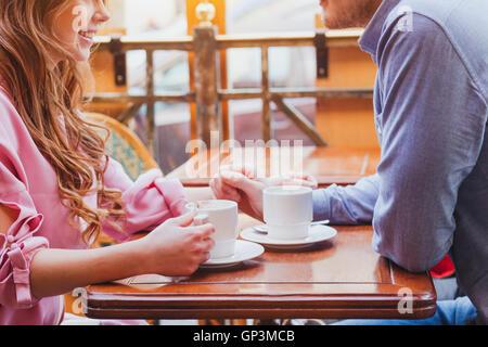 Dating, mains de couple dans un café confortable, boire du café Banque D'Images