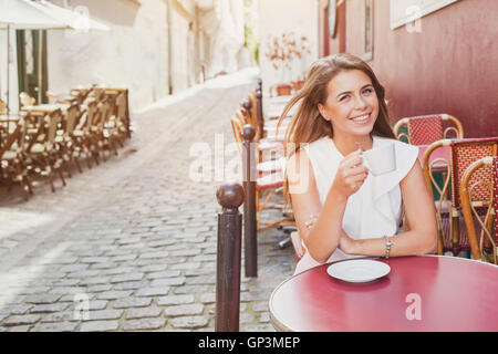 Smiling woman drinking coffee in street cafe Banque D'Images