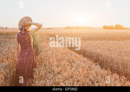 Heureux l'été jeune femme en champ de blé par le coucher du soleil, la rêverie, belle arrière-plan avec place pour Banque D'Images