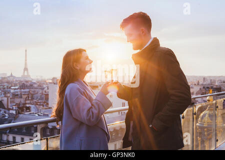Happy couple drinking champagne and smiling at sunset in Paris, célébration Banque D'Images