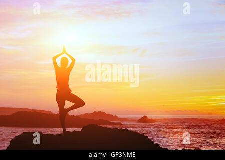 Beau fond yoga, silhouette de femme sur la plage au coucher du soleil, la pleine conscience Banque D'Images