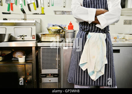 Chef standing in commercial kitchen with arms folded, mid section Banque D'Images