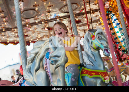 Little girl riding on carousel Banque D'Images