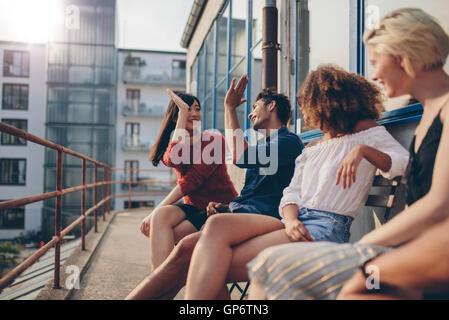 Groupe multiracial d'amis s'amusant en balcon et offrant un rapport 5. Les jeunes bénéficiant d'une terrasse. Banque D'Images