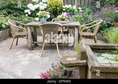 Table et chaises en bois dans un jardin ornemental avec étang Banque D'Images