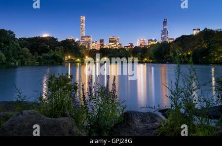 Le lac de Central Park, au crépuscule. Les lumières de la ville de New York et de Manhattan Midtown gratte-ciel Banque D'Images