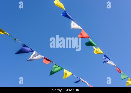 Les drapeaux de prières sur ciel bleu au Népal Banque D'Images
