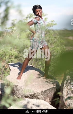 Jeune femme posant sur un rocher Banque D'Images