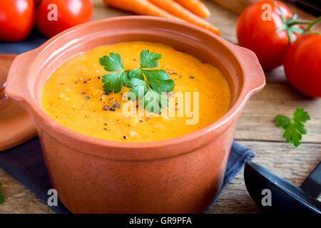 Soupe de tomates et carottes Légumes en pot en céramique et les ingrédients sur fond de bois rustique Banque D'Images