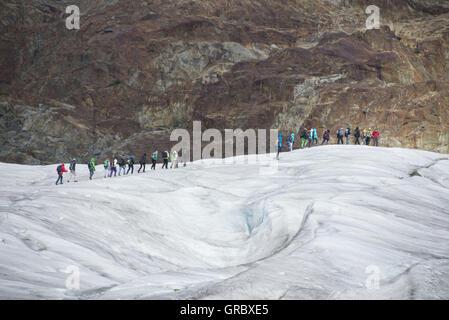 Un groupe de personnes marche sur le glacier d'Aletsch
