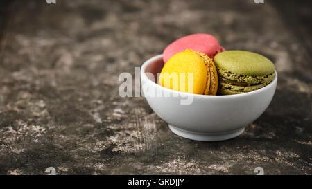 Macarons faits maison servis dans un petit bol. Banque D'Images