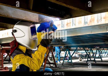Réparer les dégâts des travailleurs face inférieure de l'emballage extérieur , industriel , gros plan de soudure Banque D'Images