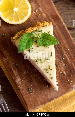 Délicieux morceau de gâteau au fromage au citron faits maison à la menthe sur fond de bois rustique, Close up Banque D'Images