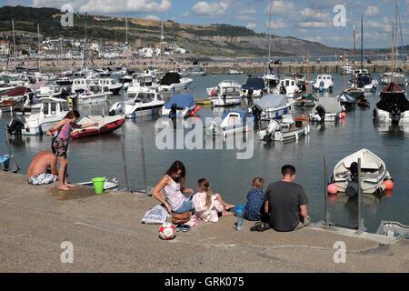 Une famille assise sur le quai par le Cobb en vue de bateaux dans le port en été à Lyme Regis Dorset England UK Banque D'Images