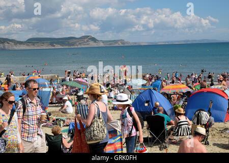 Les familles de personnes appréciant le soleil météo août ensoleillé à la fin de l'été sur la côte plage à Lyme Banque D'Images