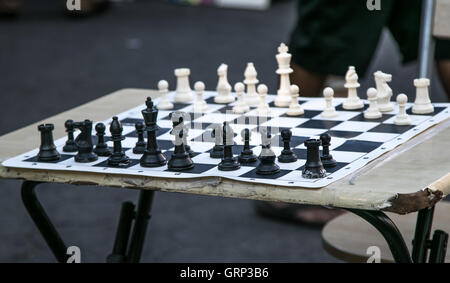 Un échiquier sur une table pliante avec tous les éléments définis pour le début de la partie.