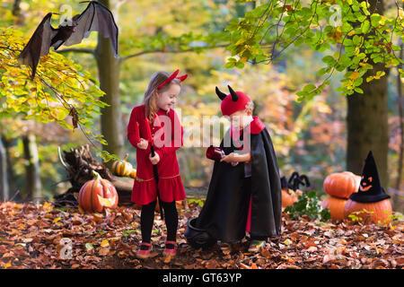 Deux drôles kids wearing devil costume vampire et avec des cornes rouges et trident trick or treating sur Halloween. Banque D'Images