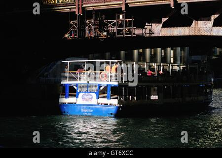 Un taxi d'eau de Chicago/bateau d'attrape un morceau de la fin de la lumière du jour en passant sous un pont sur Banque D'Images