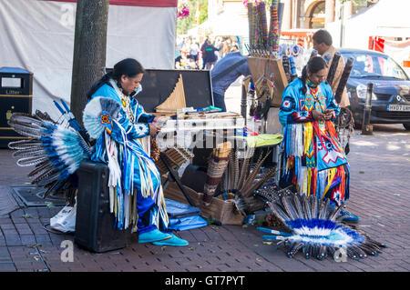 Musiciens en robe traditionnelle native American en utilisant leurs smartphones, Marché, Carlisle, Cumbria, Angleterre