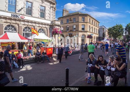 Un groupe de jeunes femmes eating Chinese food sur un banc à l'extérieur de HSBC et Barclays Bank Market Place, Carlisle, Cumbria, Angleterre en été