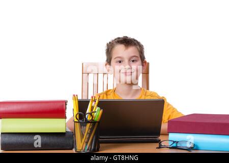 Smiling little boy at desk with laptop dans entre des piles de livres et de grande tasse de crayons et stylos Banque D'Images