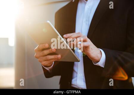 Portrait d'un jeune businessman in suit holding tablet pc outdoors