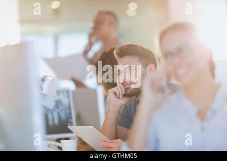 Pensive businessman using digital tablet in office Banque D'Images