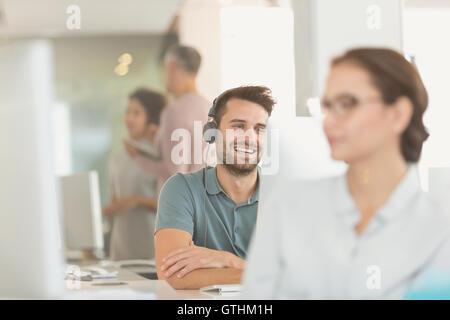 Smiling businessman créative avec des écouteurs vidéoconférence à computer in office Banque D'Images