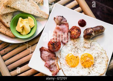 English british classique petit-déjeuner avec des oeufs au plat bacon saucisse tomates et toasts définir Banque D'Images