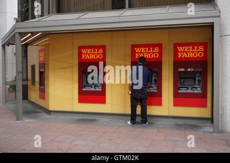 Un homme est à un guichet automatique, Wells Fargo Wells Fargo Bank storefront, San Francisco, Californie Banque D'Images