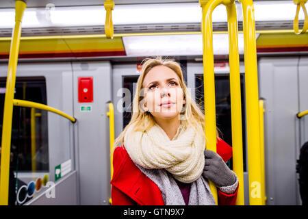 Belle jeune femme en robe rouge dans Subway train Banque D'Images