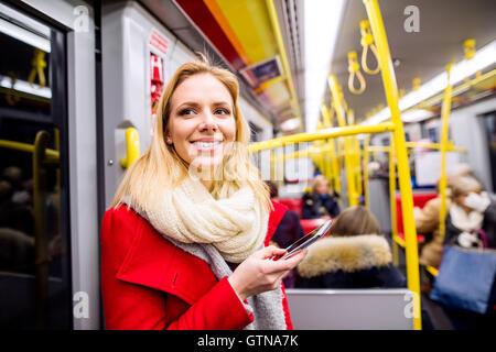 Belle jeune femme avec smart phone in Subway train Banque D'Images