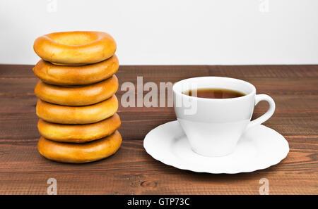 Bouquet de délicieux bagels rose et blanc à côté d'une tasse de thé sur la soucoupe se coucher sur une table en Banque D'Images