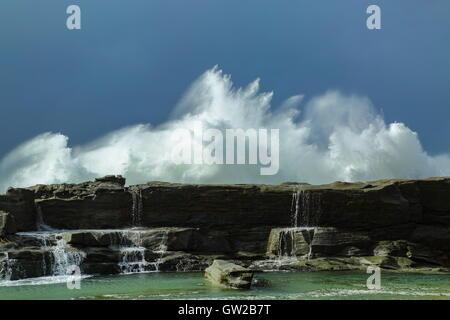 Une tempête hivernale whips de grandes et puissantes vagues qui s'écraser sur une plage, sous un ciel lourd. Banque D'Images