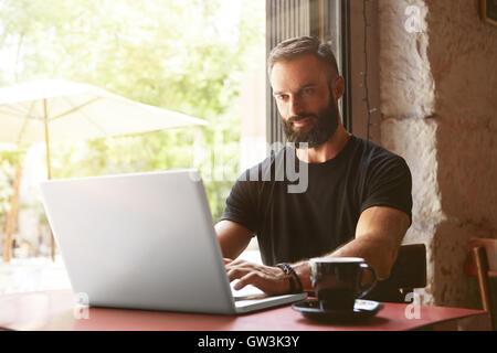 Handsome Businessman Wearing Barbu Tshirt noir pour ordinateur portable Table de travail bois urbains Cafe.Jeune Banque D'Images