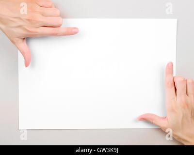 Femme mains châssis sur la feuille de papier vierge. Modèle avec copie espace Banque D'Images