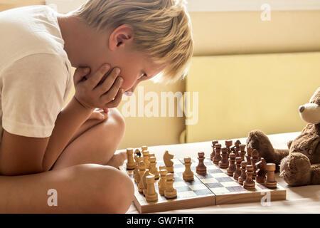 Garçon enfant jouant aux échecs à la maison, jeu intellectuel, teinte et selective focus