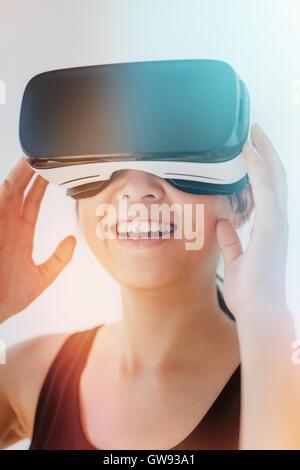 Close up shot of young woman en utilisant le casque de réalité virtuelle contre l'arrière-plan gris avec effet sunflare. Banque D'Images