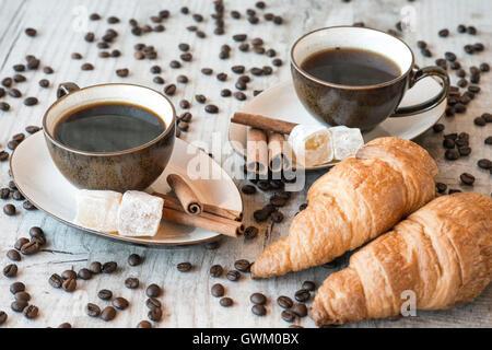 Tasse de café avec des grains, croissant sur fond de bois Banque D'Images