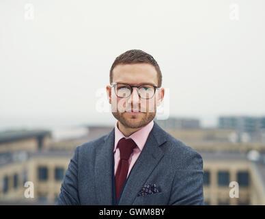 Déterminé d'intenses young businessman wearing glasses debout sur la terrasse extérieure d'un immeuble à regarder Banque D'Images