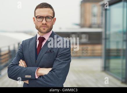 Confiant classy businessman wearing glasses debout sur un balcon en plein air à la recherche de l'appareil photo Banque D'Images
