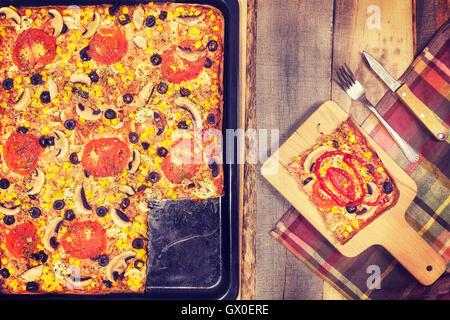 Des tons Vintage pizza au thon avec des tomates, des olives, l'oignon et le maïs sur fond de bois, vue du dessus. Banque D'Images