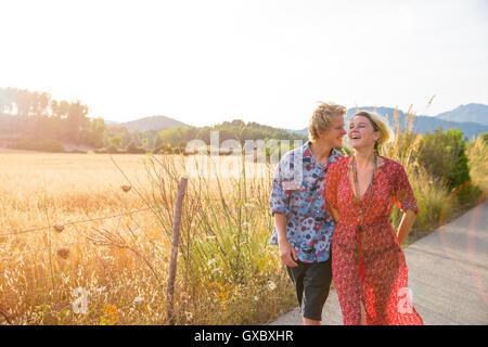Jeune couple de rire tout en flânant le long de la route rurale, Majorque, Espagne Banque D'Images