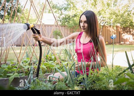 Jeune femme des plantes de l'eau dans jardin avec arrosage Banque D'Images