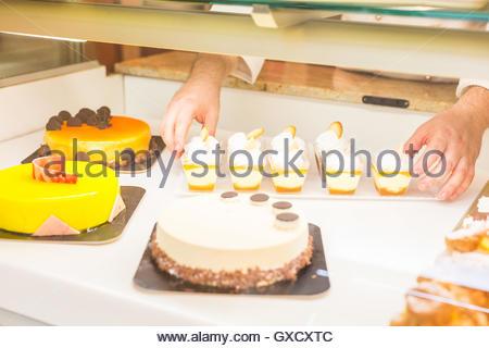 Baker organiser des gâteaux dans le cabinet d'affichage Banque D'Images