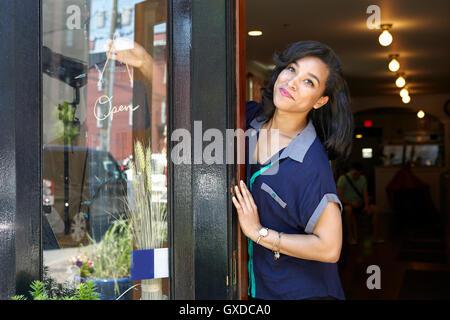Travailleur féminin en boulangerie, debout dans la porte, se tournant pour ouvrir Banque D'Images