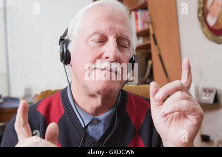 Senior man listening to music on écouteurs à la maison Banque D'Images