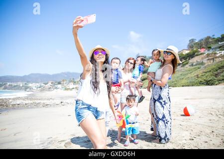 Mère de prendre des selfies et amis des bébés sur beach, Malibu, California, USA Banque D'Images
