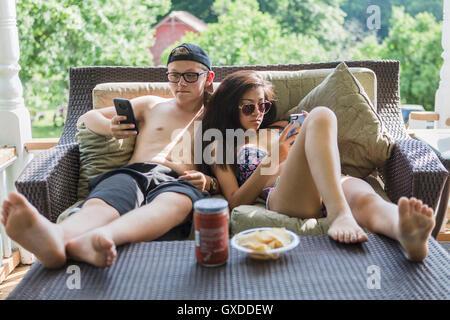 Woman wearing bikini et short de vous coucher sur un canapé patio smartphones lecture Banque D'Images
