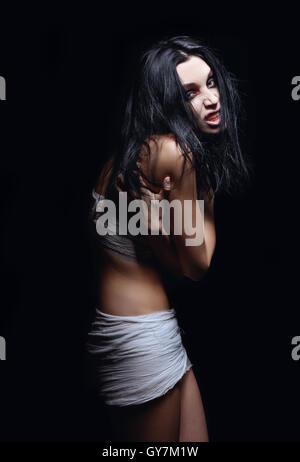 Coup d'horreur: portrait de jeune fille en colère contre le mal parmi l'obscurité Banque D'Images